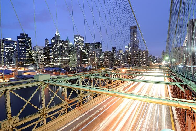 View of downtown Manhattan from the Brooklyn Bridge with traffic flying by..jpeg